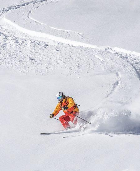 one man skiing, white snowy background, deep powder snow